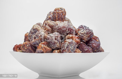 963384046 istock photo Arabian dates with nuts in white bowl 1001750118