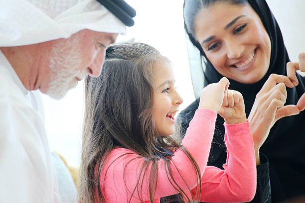 Arabian family making heart symbols with hands in a cafe Arabian family enjoying leisure time in a cafe saudi arabia stock pictures, royalty-free photos & images