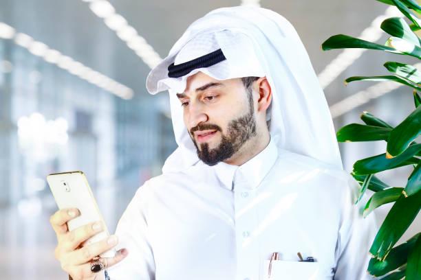 hombre árabe usando un teléfono celular. - qatar fotografías e imágenes de stock