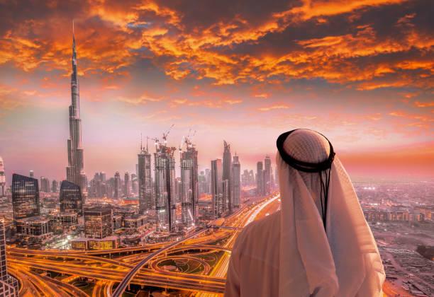 arabische mann beobachtet stadtbild von dubai mit modernen futuristischen architektur in vereinigten arabischen emiraten. - dubai urlaub stock-fotos und bilder