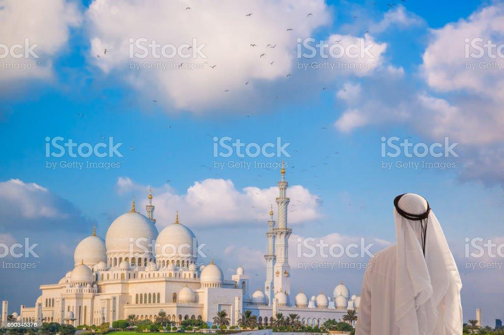 Arabian man watching Sheikh Zayed Grand Mosque in Abu-Dhabi, United Arab Emirates stock photo