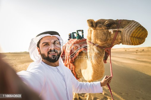 491496340 istock photo Arabian man with camel in the desert 1166640503