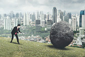 Arabian male manager pulling a stone while climbing on the hill with modern city background