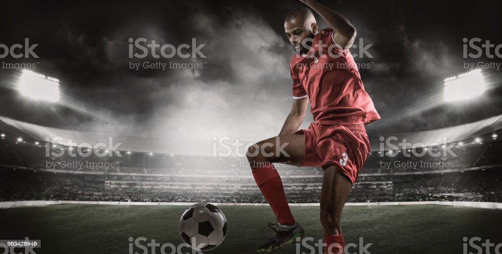 Arabian Muslim Non-Caucasian Football Player controlling a Soccer Ball in a floodlit stadium - Zbiór zdjęć royalty-free (Afroamerykanin)