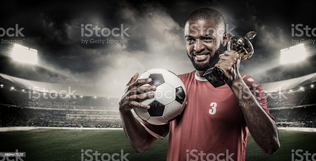 Arabian Holding de joueur musulman pour la Football de le Non-caucasienne un ballon de football sur des feux de stade - Photo de Adulte libre de droits