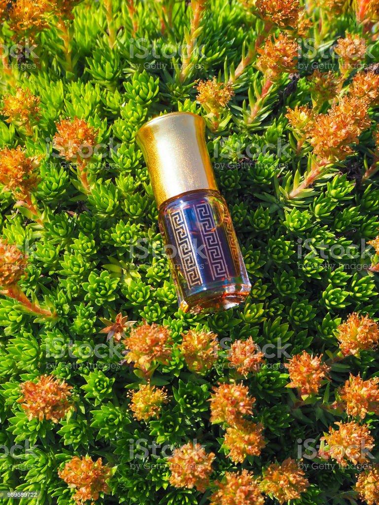 Arabian oud attar perfume or agarwood oil fragrances in mini bottles on a natural background. stock photo