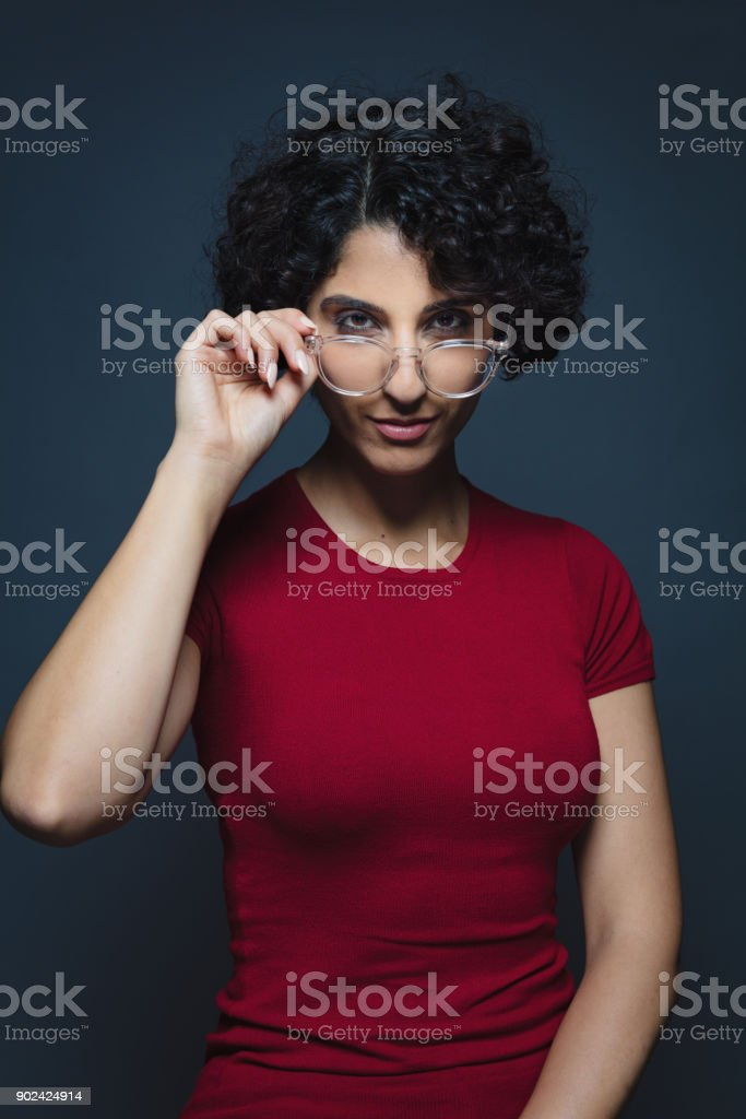 Arabian woman grinning, examining looking over eyeglasses stock photo