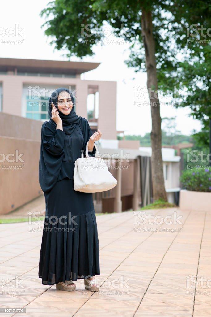 Mujer árabe teléfono de hablar y caminar. - foto de stock