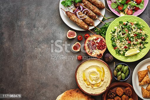 istock Arabic and Middle Eastern dinner table. Hummus, tabbouleh salad, Fattoush salad, pita, meat kebab, falafel, baklava, pomegranate. Set of Arabian dishes.Top view, copy space 1171983475