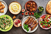 Arabic and Middle Eastern dinner table. Hummus, tabbouleh salad, Fattoush salad, pita, meat kebab, falafel, baklava, pomegranate. Set of Arabian dishes.Top view, flat lay.