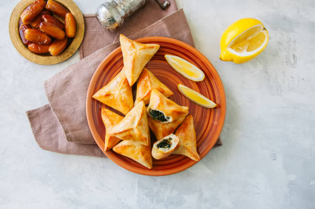 arabic and middle eastern food concept. fatayer sabanekh - traditional arabic spinach triangle hand pies dates and tea on a white stone background. top view. - samosa stock photos and pictures