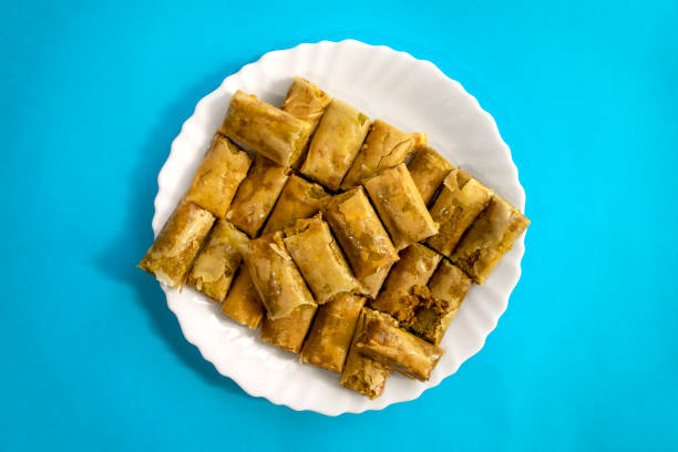 Arabic baked sweets in white plate on blue bright background. Mini Baklawa stock photo