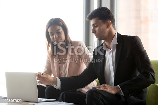 1085713886 istock photo Arabic business advisor speaking presenting african client offer with laptop 1128967622