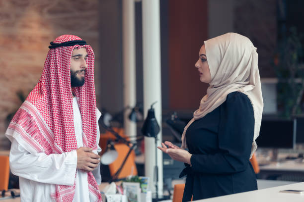arabic business couple working together on project - saudi woman stock photos and pictures