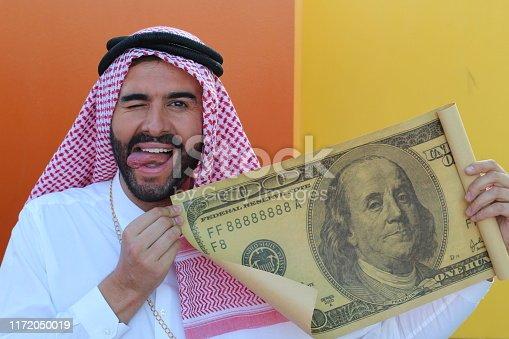 istock Arabic businessman showing a gigantic 100 dollars bill 1172050019
