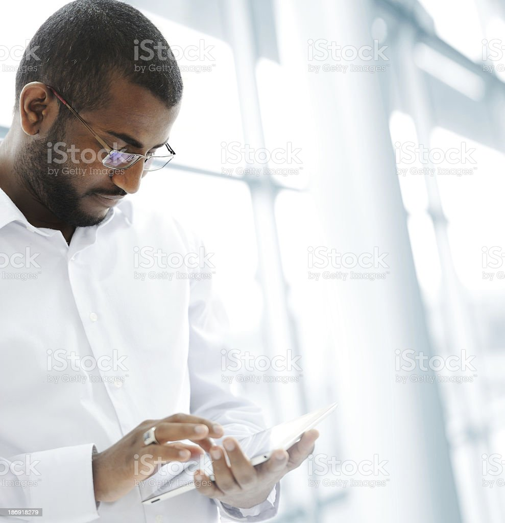 Arabic businessman using tablet inside bright white office stock photo