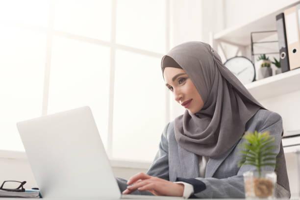 arabic businesswoman in hijab working at office - скромная одежда стоковые фото и изображения