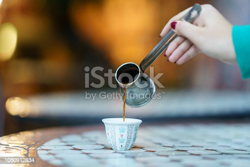 Hand pouring hot Arabic Coffee into a cup