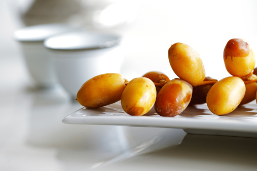 Arabic dates on a white plate with coffee cups