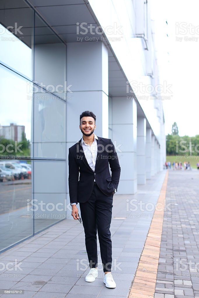 89ef8e97a3f Arabic guy in business center stands smiling walking slow - Stock image .