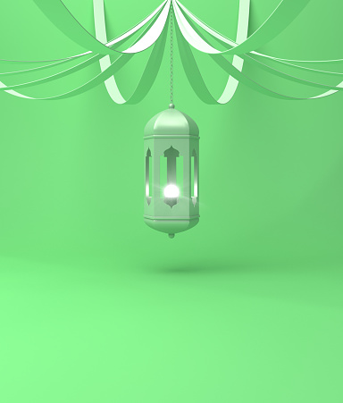 istock Arabic hanging lantern with ribbon on green pastel background. 1142727636