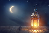 "Ornamental Arabic lantern with burning candle glowing at night. Festive greeting card, invitation for Muslim holy month Ramadan Kareem.""n"