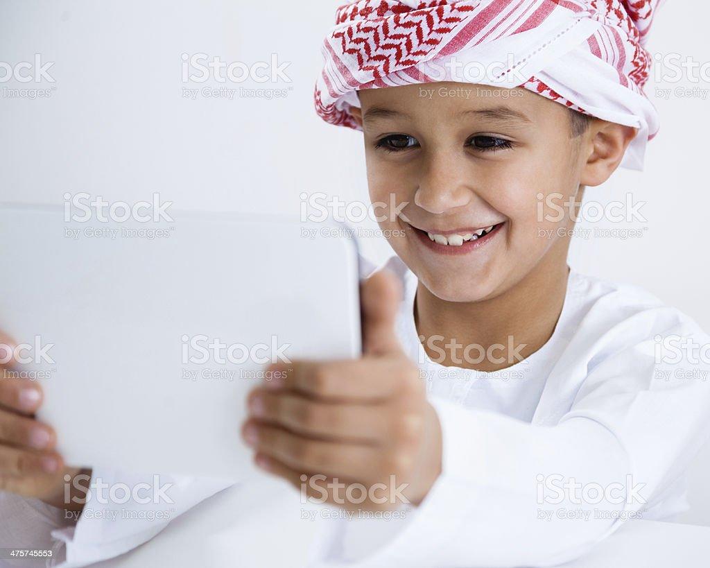 Arabic little boy using tablet stock photo