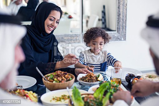 Middle Eastern family eating lunch at home, mother is serving to her son.