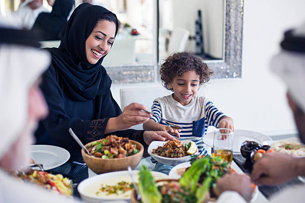 Arabic lunch time Middle Eastern family eating lunch at home, mother is serving to her son. arabia stock pictures, royalty-free photos & images