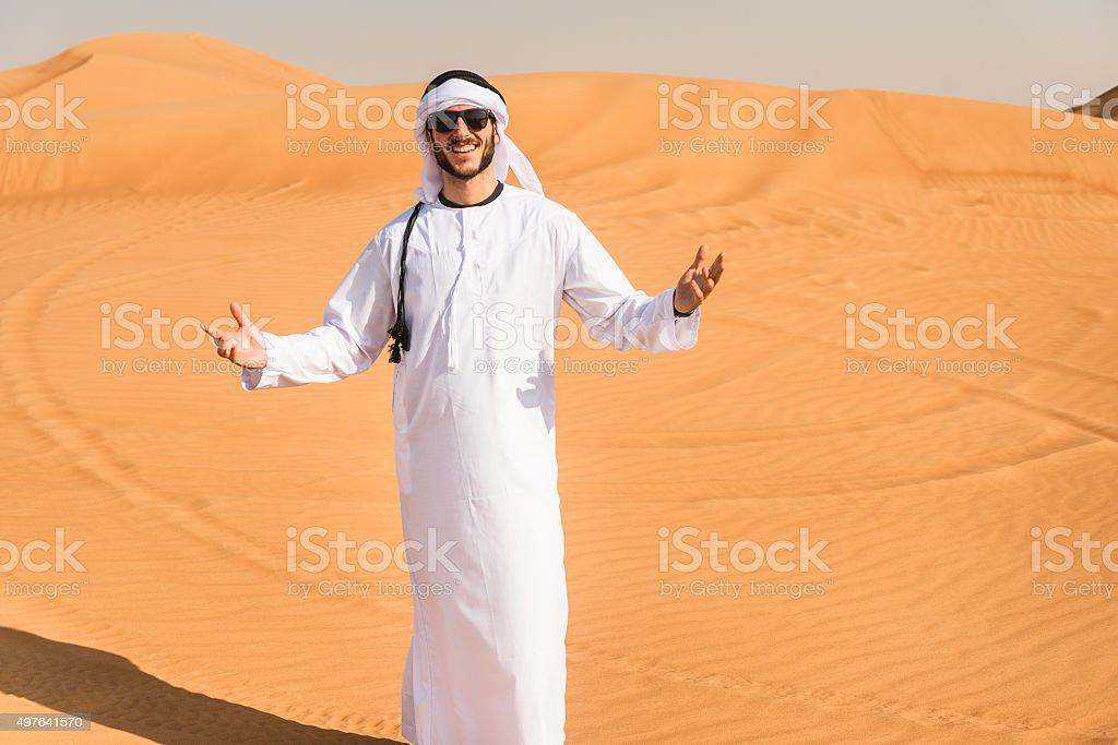 arabic man smiling on the desert stock photo