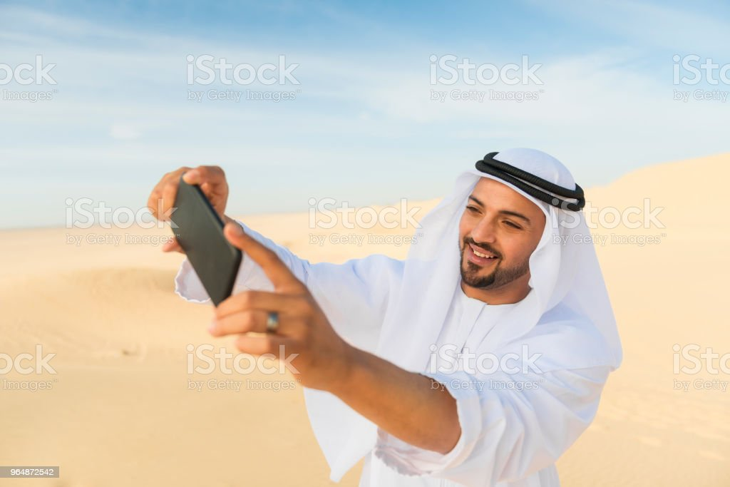 Arabic man taking a selfie in the desert royalty-free stock photo