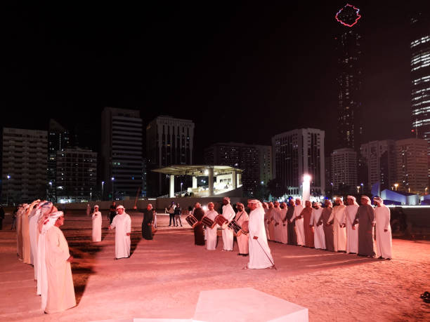arabic middle eastern men performing a traditional dance in abu dhabi, uae at night - uae national day стоковые фото и изображения