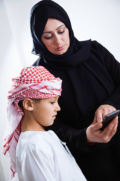 Arabic mother and her son using smart phone stock photo