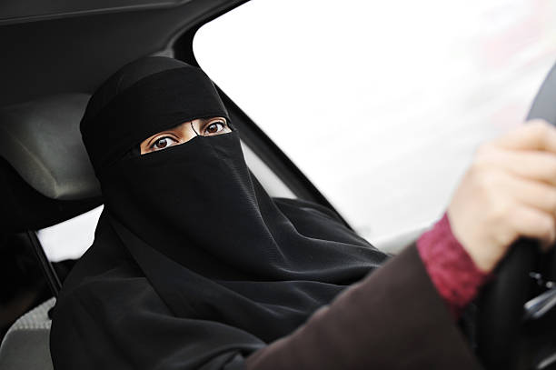 arabic muslim woman with veil and scarf  driving car - saudi woman stock photos and pictures