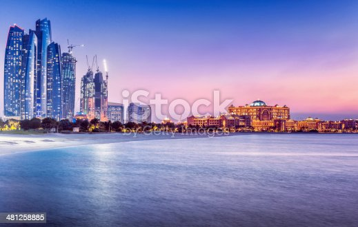View over the Persian Gulf on Abu´s Dhabi´s skyline, with the landmarks Etihad Towers, newly built skyscrapers and the Emirates Palace at dusk.