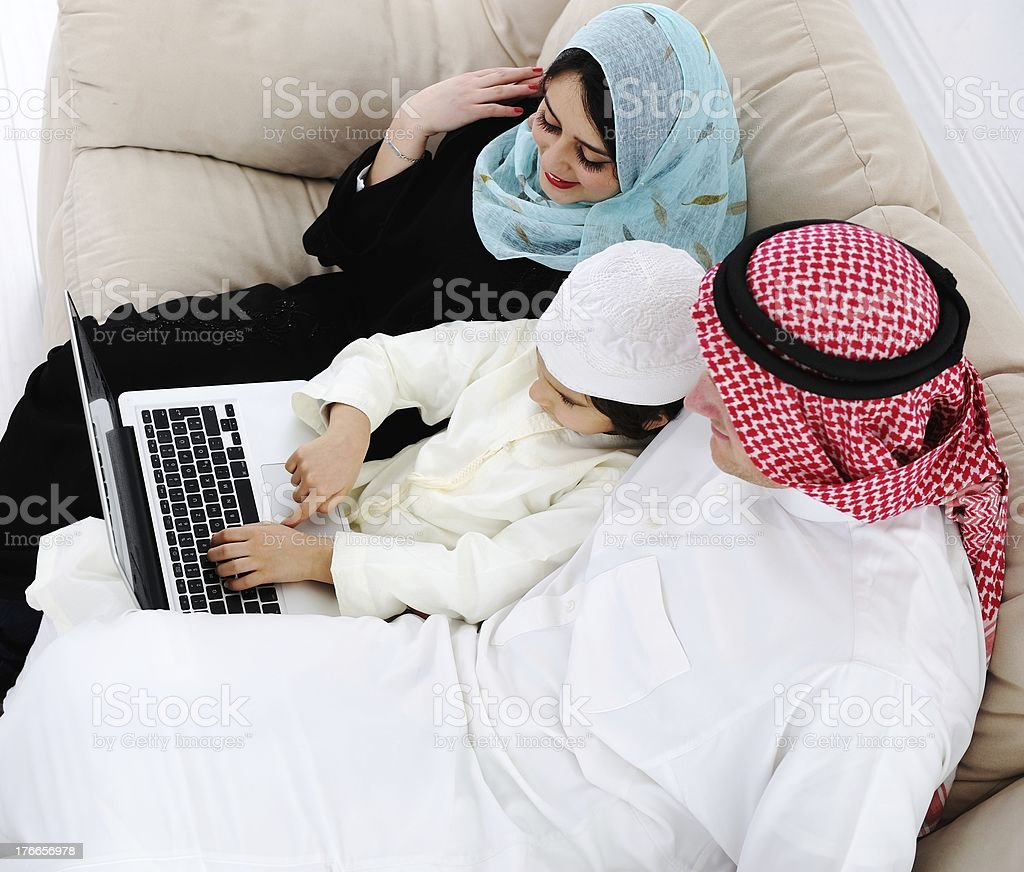 Arabic parents and little boy at home with laptop computer royalty-free stock photo