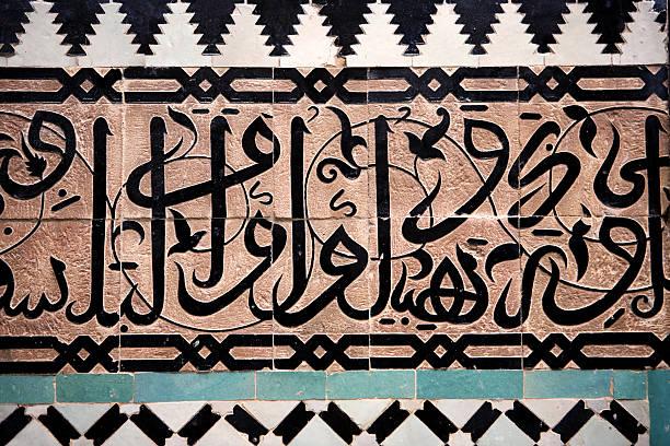 Arabic script on tiled wall in black, white, tan, and Aqua stock photo