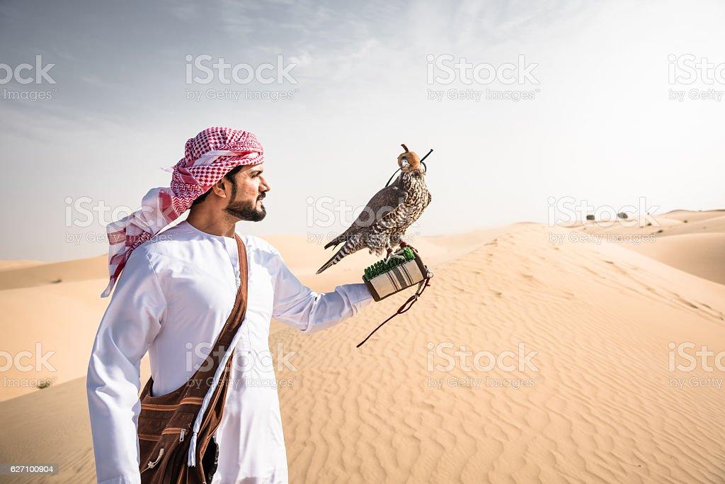 arabic sheik on the desert holding a falcon stock photo