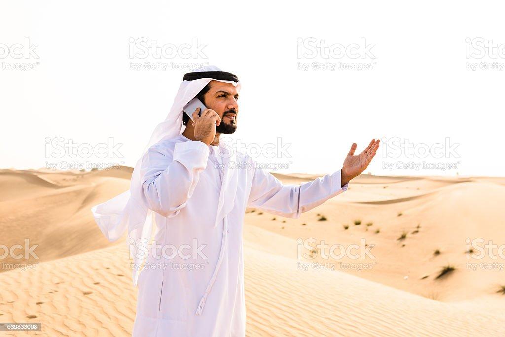 arabic sheik on the phone on the desert stock photo
