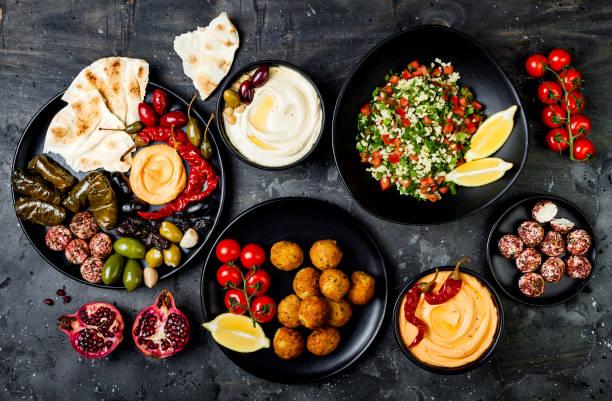 Arabische Küche. Orientalische Meze-Platte mit Fladenbrot, Oliven, Hummus, gefüllten Dolma, Labneh Käsebällchen in Gewürzen. Mediterrane Vorspeise Partyidee – Foto