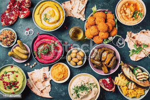 istock Arabic traditional cuisine. Middle Eastern meze with pita, olives, colorful hummus, falafel, stuffed dolma, babaganush, pickles, vegetables, pomegranate, eggplants. Mediterranean appetizer party idea 1271870386