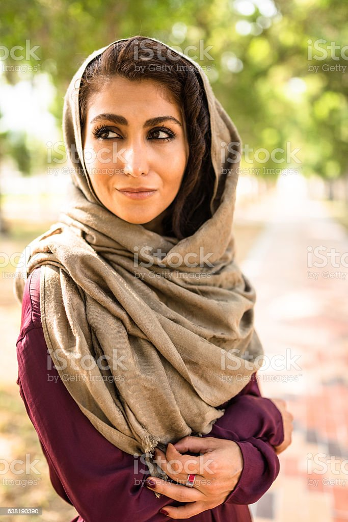 arabic woman in the park in abu dhabi - uae stock photo