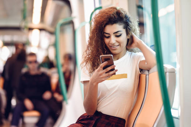 Arabic woman inside subway train looking at her smartphone stock photo