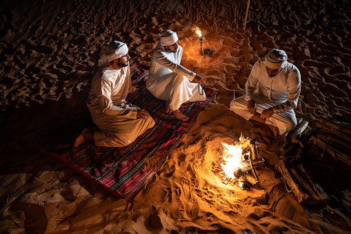 Arabs camping at night in the desert out of Dubai