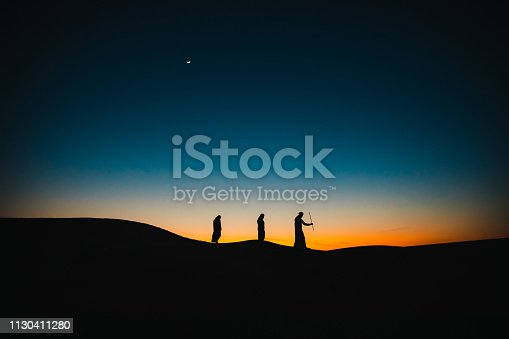 Arabs, Middle East, Culture - Three Arab men walking behind each other on the sand dunes