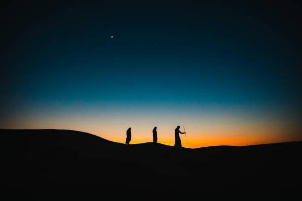 araber auf den sanddünen, die in der dämmerung hintereinander laufen - eid stock-fotos und bilder