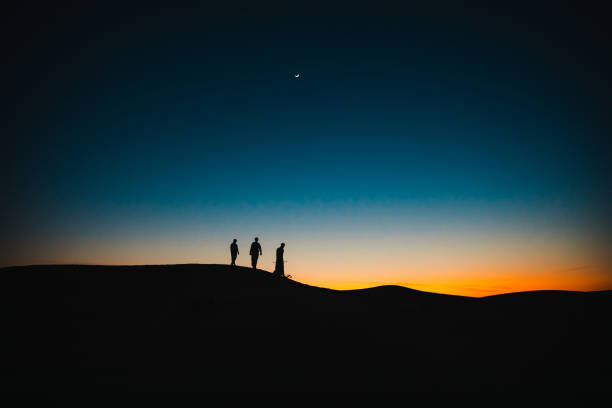 Arabs on the sand dunes walking behind each other during twilight stock photo
