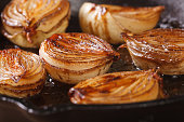 ñaramelized onion halves with balsamic vinegar in a pan close-up, horizontal