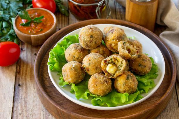 아란치니. 모 짜 렐 라와 햇볕에 말린 토마토, 나무 테이블에 토마토 소스가 들어간 이탈리안 라이스 볼. 스톡 사진