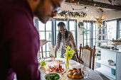 Couple arranging Christmas table for a Christmas dinner